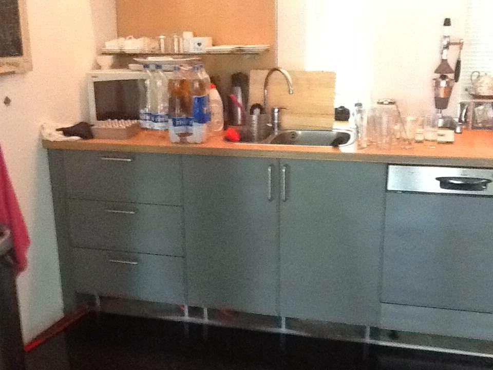 Keuken – Grijze deuren/lades en een houten aanrechtblad, naar ...